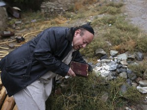 Zabulon Simantov, an Afghan Jew, prays at a Jewish cemetery in Kabul