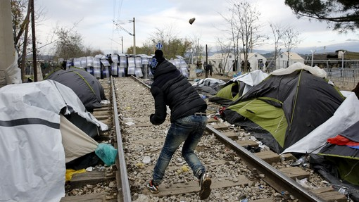 A stranded migrant throws a stone at a Macedonian police cordon, as minor clashes broke out during a protest against the building of a metal fence at the Greek-Macedonian borders near the village of Idomeni